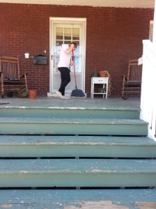 Kayla, UK Learning Service volunteer, sweeps winter off the front porch.